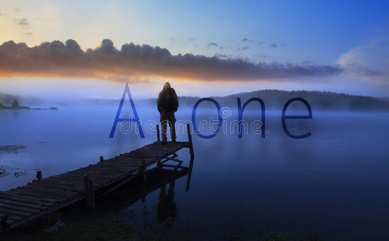 Alone man. Waching sunrise near lake, conceptual poster with word 'alone' added stock image