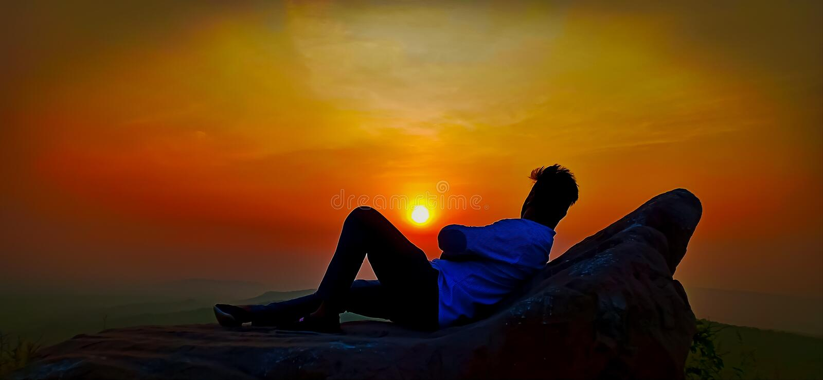Alone man watch over valley to Sun,Man relaxing in his big stone and enjoying the view from sunset,relaxing. Total relaxation,Alone man watch over valley to royalty free stock photography