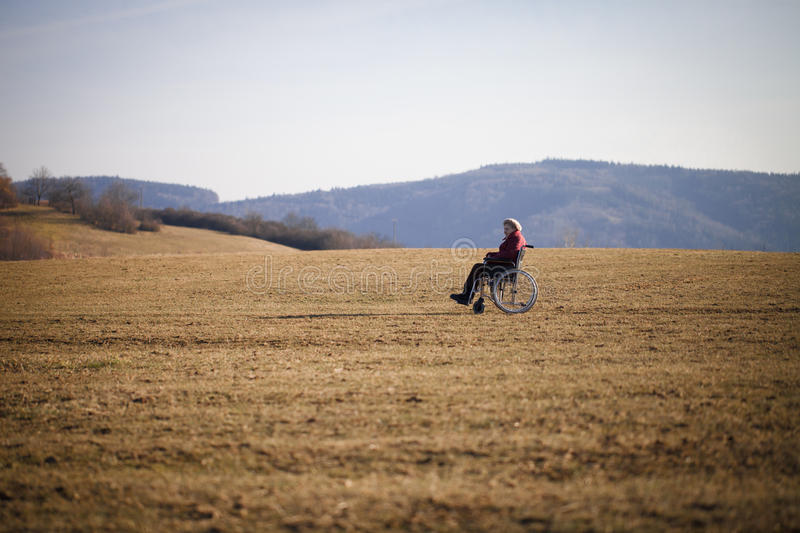 Alone old woman in wheelchair. Alone old woman on wheelchair on the field royalty free stock images
