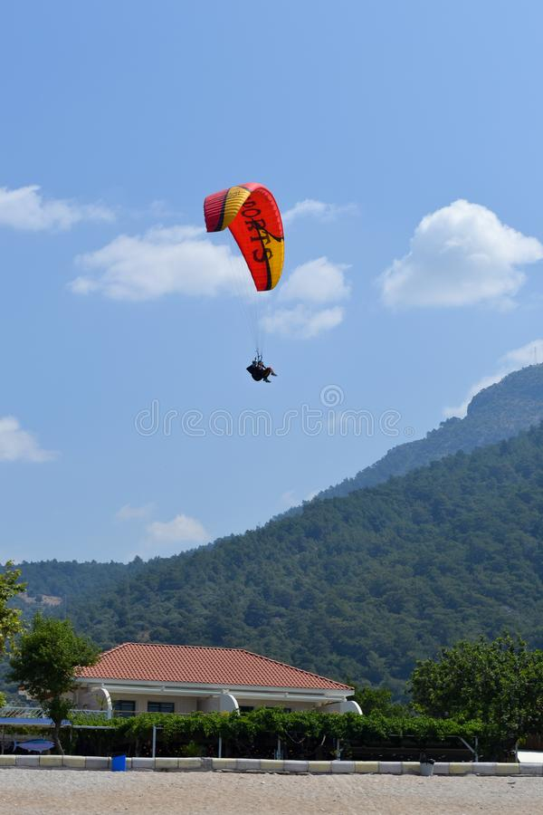 Alone paraglider flying in the blue sky against the background of clouds. Paragliding in the sky on a sunny day stock photography