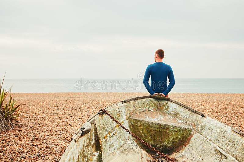 Alone and pensive man on the beach stock image