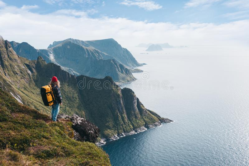 Alone professional traveler with backpack on high mountain standing on the edge cliff rock and looking away. Adventure lifestyle vacation stock photo