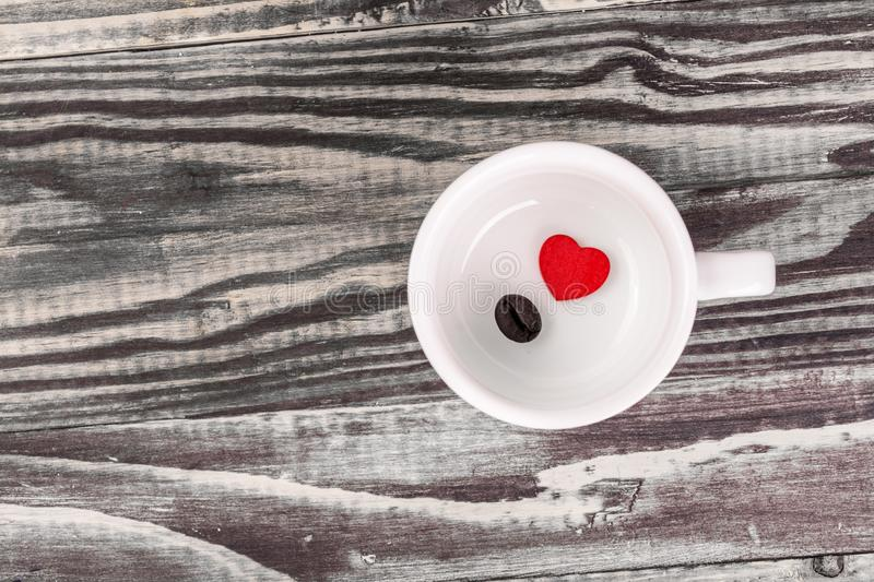Alone red heart with coffee bean. In blank cup on wood stock photography