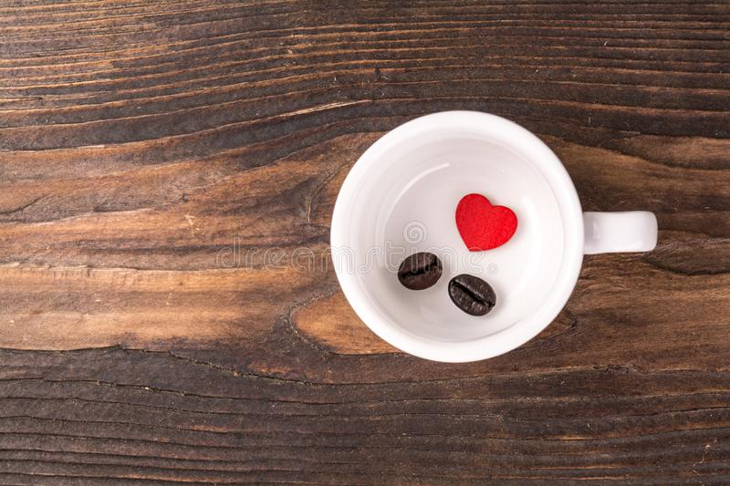 Alone red heart with coffee bean. Alone red heart with tow coffee bean in blank cup on wood royalty free stock image