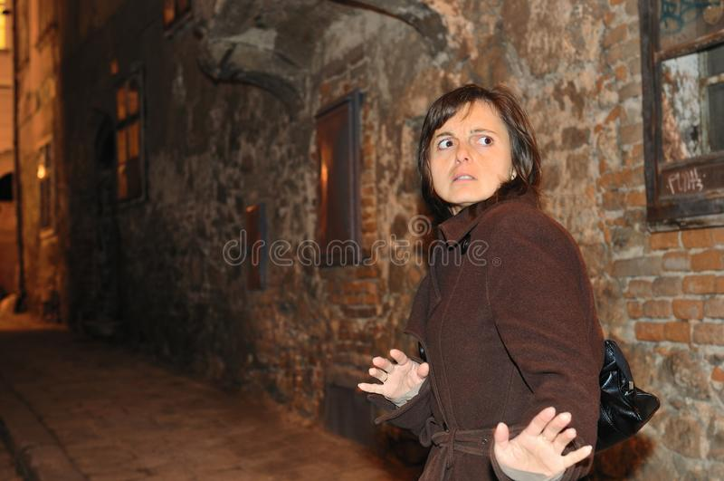 Alone on street in the night. Fear from assault - young woman alone on street in the night awaiting someone from behind stock images