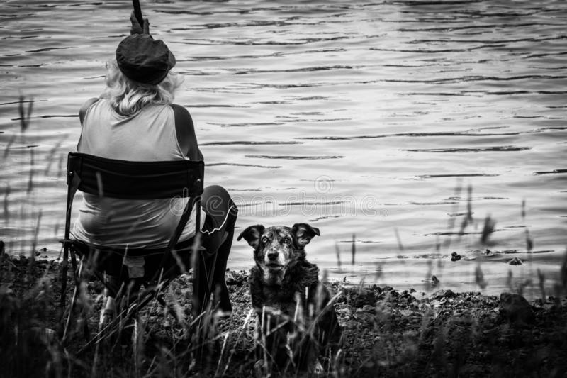 An alone woman and her guardian dog are fishing on the Cassière lake stock images