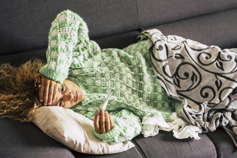 Alone woman at home lying down on the sofa looking at the thermometer with high fever themperature - sick lady with curly hair stock photo