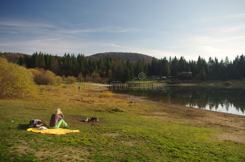 Alone woman with a picnic sitting by the lake royalty free stock photos