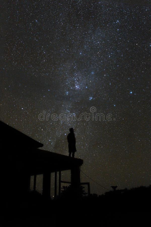 Alone woman on rooftop watching mliky way and stars in the night sky on Bali island royalty free stock image
