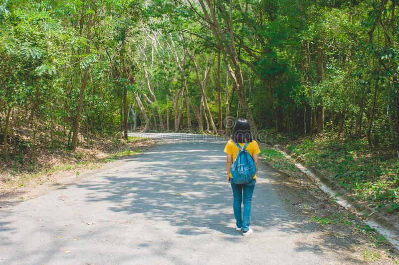 Alone woman traveller or backpacker walking along contryside road among green trees. stock photo