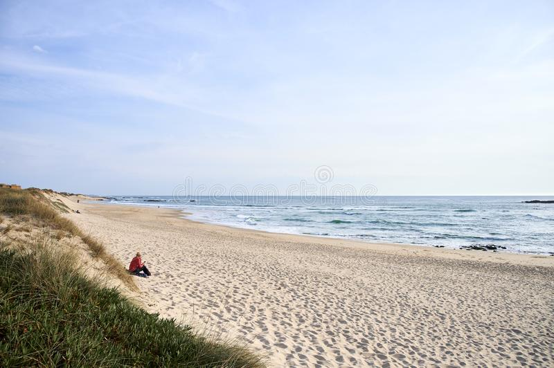 Alone women seated on the beach royalty free stock images