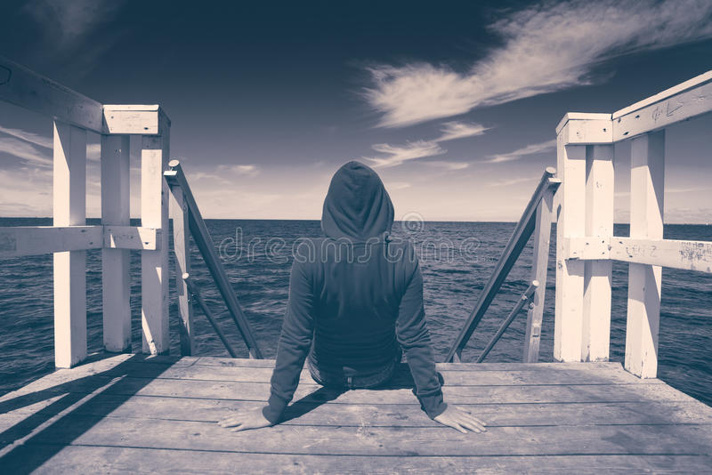 Alone Young Woman at the Edge of Wooden Pier stock image