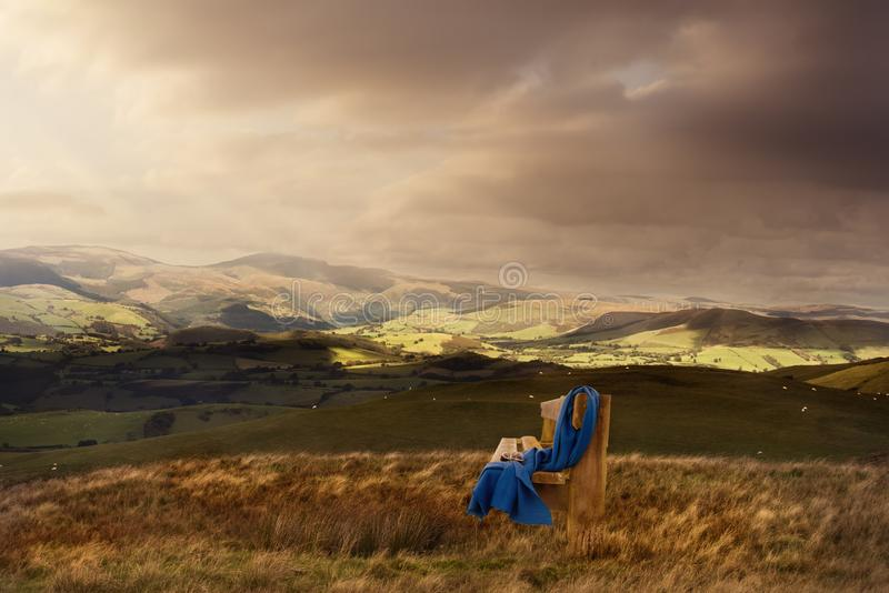 Along bench with a scarf on the top of hill against cloudy sky at the sunset. Along bench with a blue scarf on the top of hill against a lot of hills and cloudy stock photo