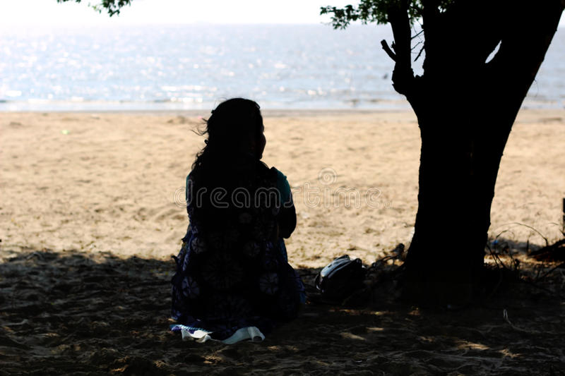 Along girl under a tree royalty free stock photography