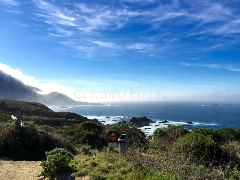 Along the Pacific coast highway, California. Ocean next to the Pacific coast highway and the mountains behind the mist, California royalty free stock images