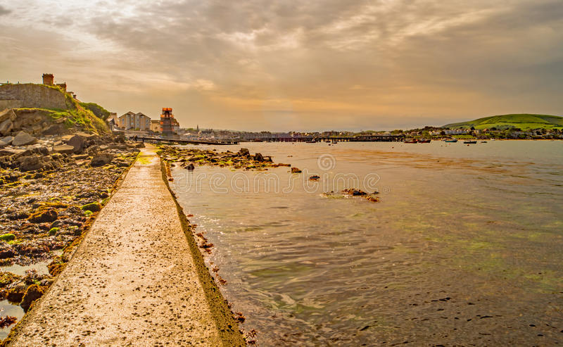 A look back along the straight and narrow coast path to Swanage. A view back along the narrow coast path at Swanage leading along the sea to Peveril Point stock images
