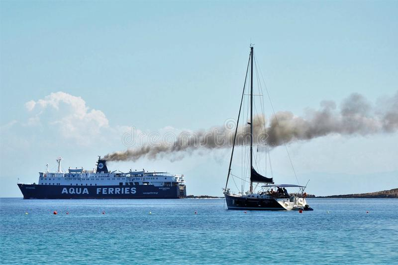 Alonissos, Greece – June 28, 2016: Cruise ferry ship on sea with big black smoke streak line from its chimneys. In contrast to a small fishing boat royalty free stock photography