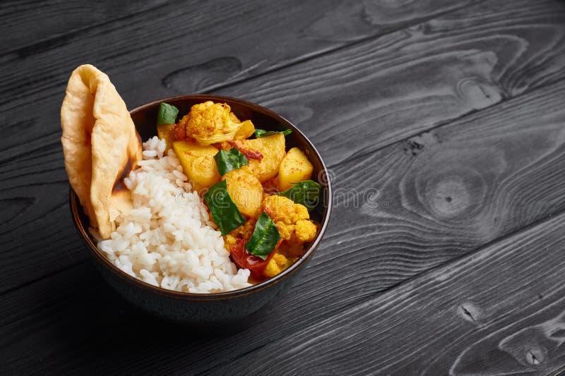 Aloo Gobi con arroz y el chapati Curry vegetariano de la cocina india en el fondo de madera negro fotografía de archivo