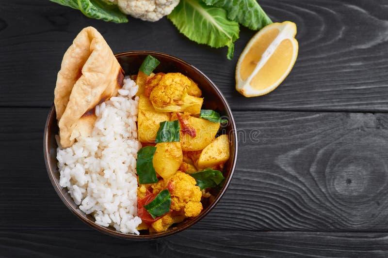 Aloo Gobi con arroz y el chapati Plato vegetariano de la cocina india adornado con el limón y la coliflor imagen de archivo
