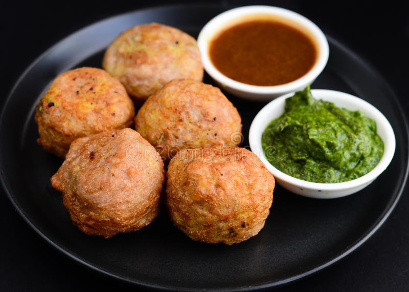Aloo vada or aloo bonda. Hot fried vada for vada-pa.Indian street food served with mint and tamarind chutney in Maharashtra stock images