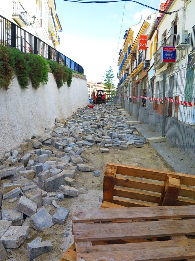 Alora Spanien - November 7, 2018: Fyrkantstenläggningstenar som rivas sönder ut i bygata i Andalusia royaltyfri bild