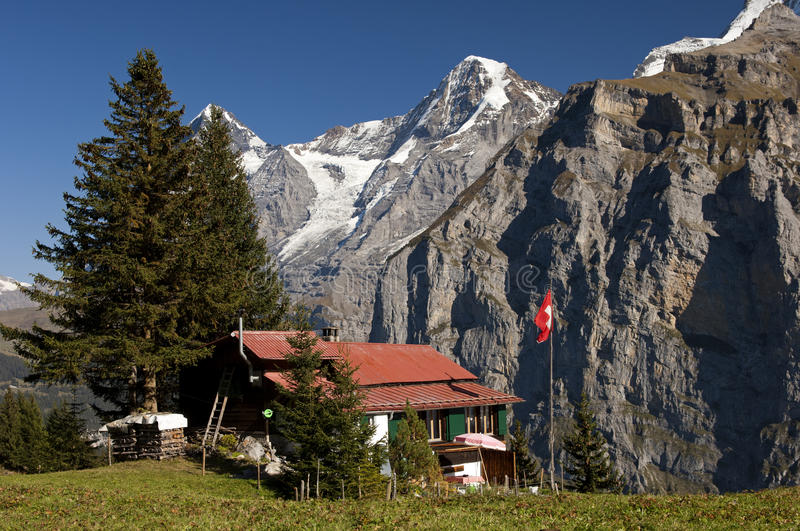 Alp with farm house. In front of Mt. Eiger and Mt Moench, Muerren, Bernese Oberland, Switzerland stock photo