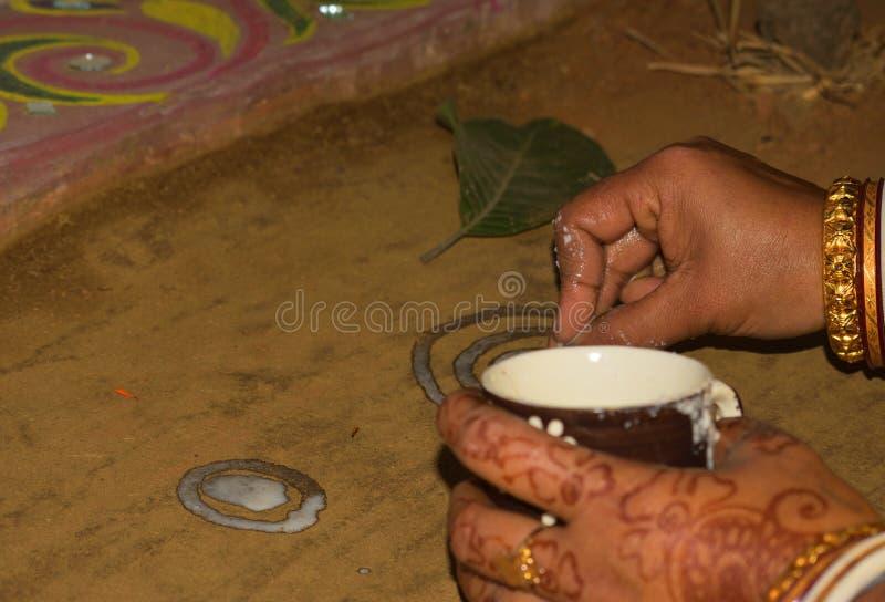Alpana u. x28; Weiße Farbe mit flüssigem Reis-Paste& x29; wird in einer Bengalihochzeitszeremonie gemalt lizenzfreie stockbilder