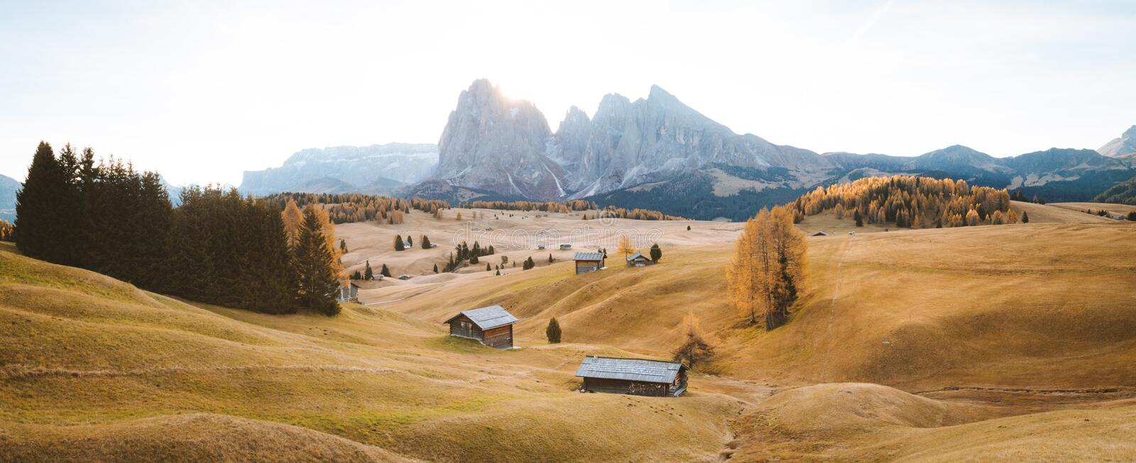Alpe di Siusi at sunrise, Dolomites, South Tyrol, Italy. Beautiful view of traditional wooden mountain chalets on scenic Alpe di Siusi with famous Langkofel royalty free stock image