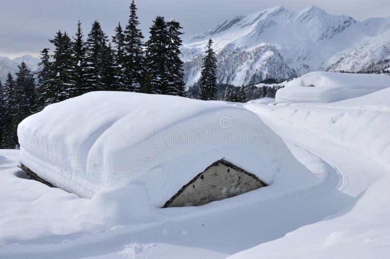 Alpenhütten bedeckt durch Schnee lizenzfreie stockfotos