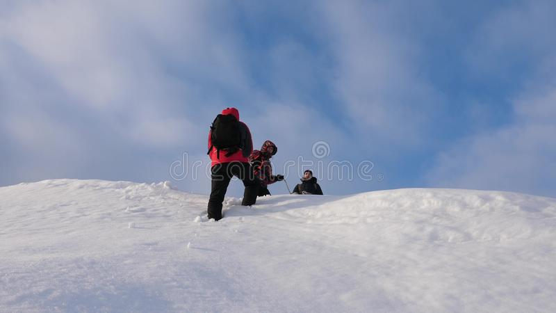 Alpenists team in winter down rope from mountain. Travelers descend by rope from a snowy hill. well-coordinated teamwork royalty free stock photos
