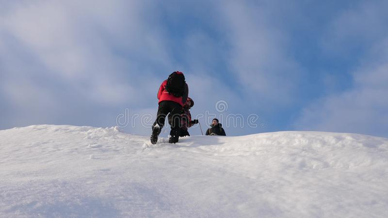 Alpenists team in winter down rope from mountain. Travelers descend by rope from a snowy hill. well-coordinated teamwork stock image