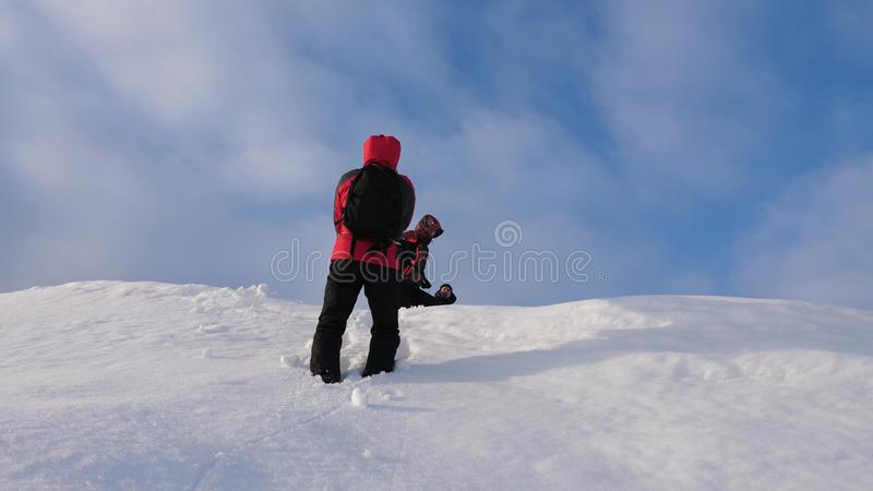 Alpenists team in winter down rope from mountain. Travelers descend by rope from a snowy hill. well-coordinated teamwork. Alpenists team in winter down rope from royalty free stock image