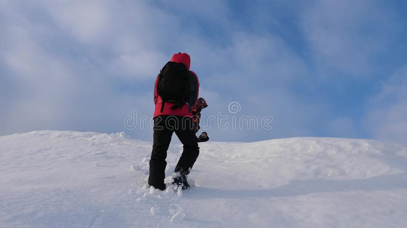 Alpenists team in winter down rope from mountain. Travelers descend by rope from a snowy hill. well-coordinated teamwork. Alpenists team in winter down rope from stock photo
