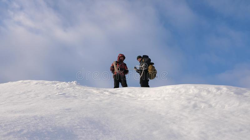 Alpenists team in winter are preparing to descend on rope from mountain. Travelers descend by rope from a snowy hill royalty free stock images