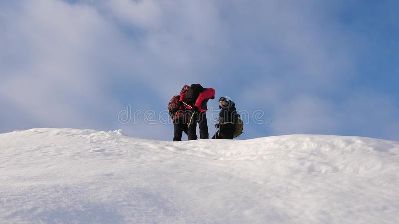 Alpenists team in winter are preparing to descend on rope from mountain. Travelers descend by rope from a snowy hill. Alpenists team in winter are preparing to royalty free stock photo