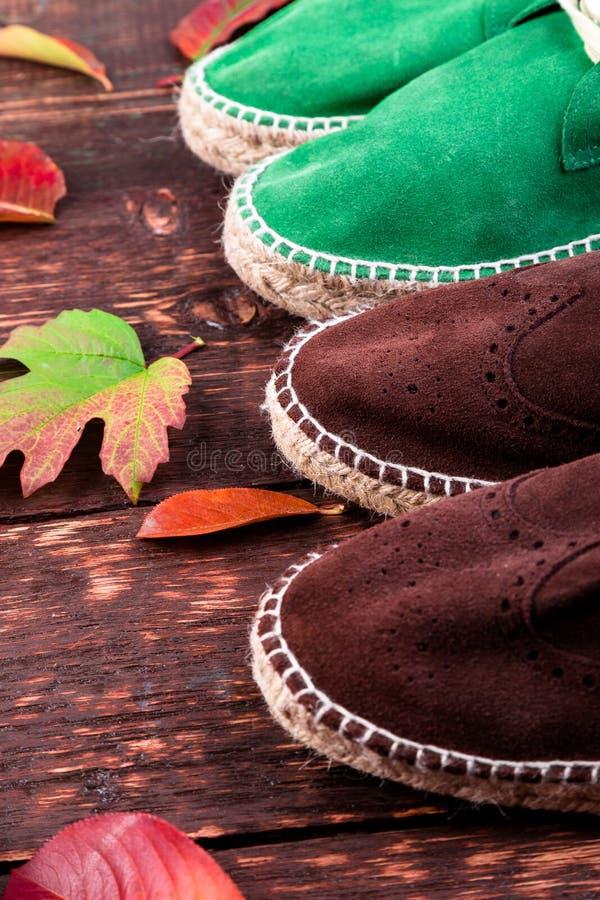 Alpergatas das botas da camurça de Brown e do homem verde em de madeira imagens de stock royalty free