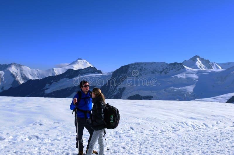 Alpes suisses : Un jeune couple marchant au-dessus de la neige chez Mönchshut au-dessus de Grindelwald/d'Interlaken photographie stock libre de droits