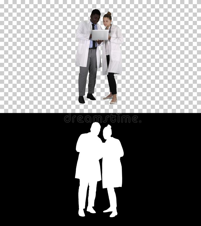 Medical staff working in front of a grey laptop while standing, Alpha Channel stock image