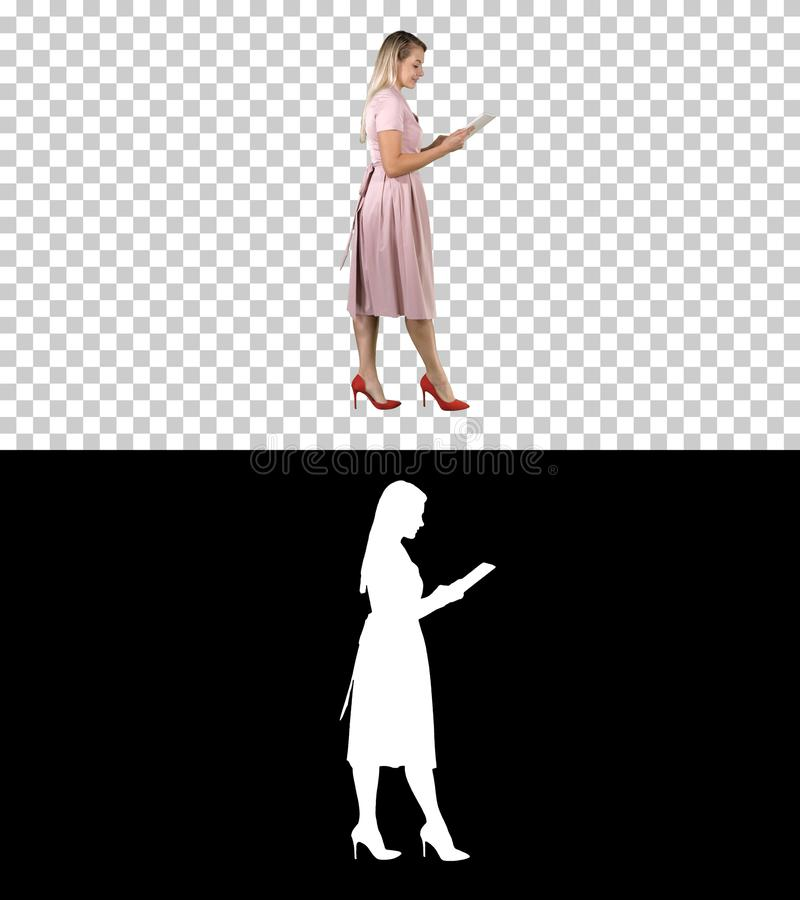 Blonde in pink dress walking and using tablet, Alpha Channel. On Alpha Matte. Full length portrait side view. Blonde in pink dress walking and using tablet royalty free illustration