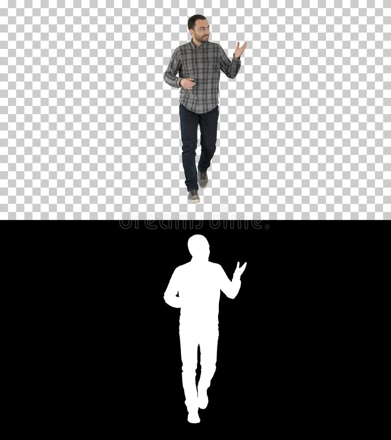 Young confident man in shirt and jeans walking towards camera and pointing to the sides, Alpha Channel stock image