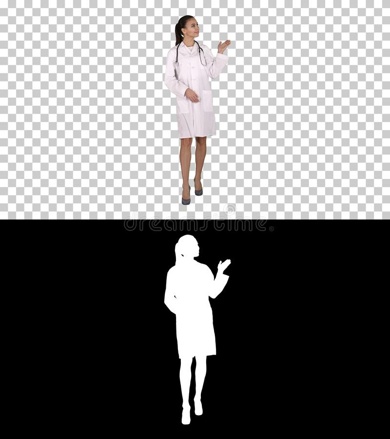 Young medical doctor woman presenting and showing product or text, Alpha Channel stock photo