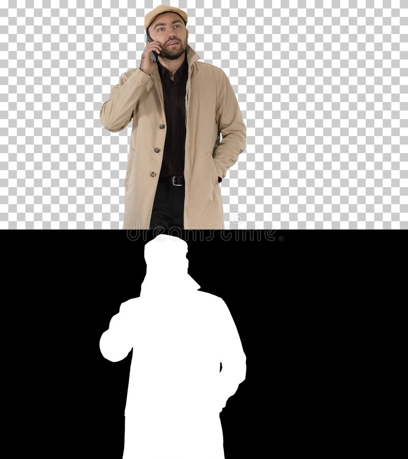 Man dressed in trench making business call while walking, Alpha Channel stock photo