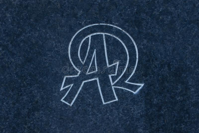 Alpha and Omega carved into stone surface. stock image