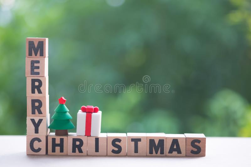 Alphabet block wooden letters Merry Christmas. With toy Christmas tree and gift box, copy space for text stock image