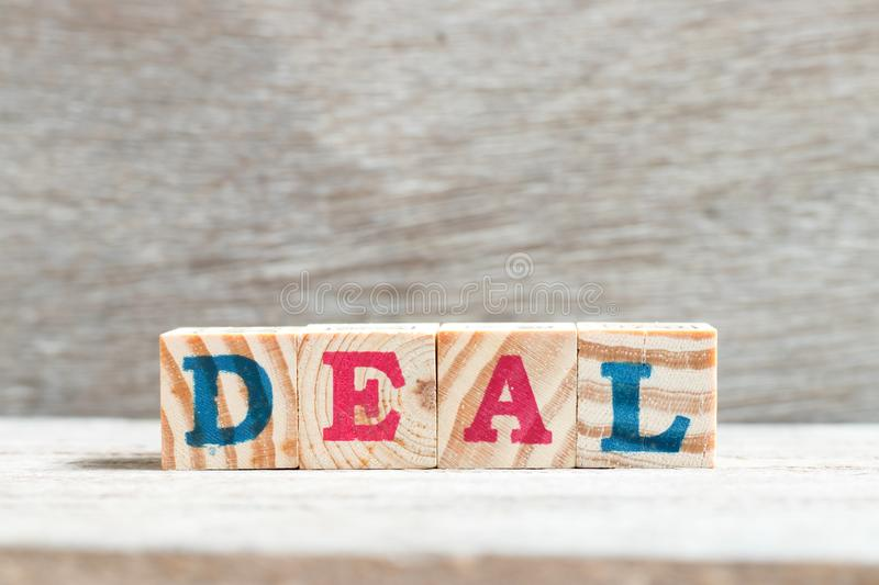 Alphabet block in word deal on wood background. Alphabet letter block in word deal on wood background stock image