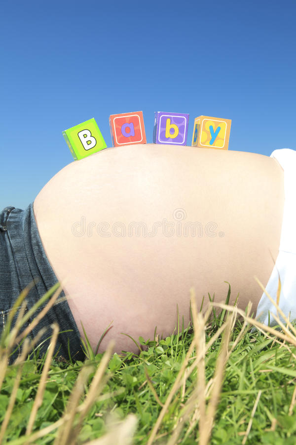 Alphabet blockiert Rechtschreibung BABY auf einem schwangeren Bauch lizenzfreie stockbilder
