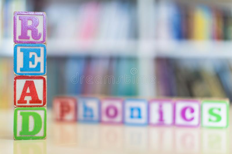 Alphabet blocks spelling the words read and phonics in front of a bookshelf royalty free stock image