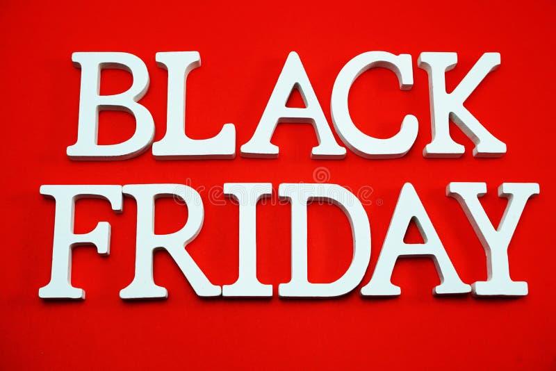 Alphabet de concept d'achats de vente de Black Friday sur le fond rouge photographie stock libre de droits