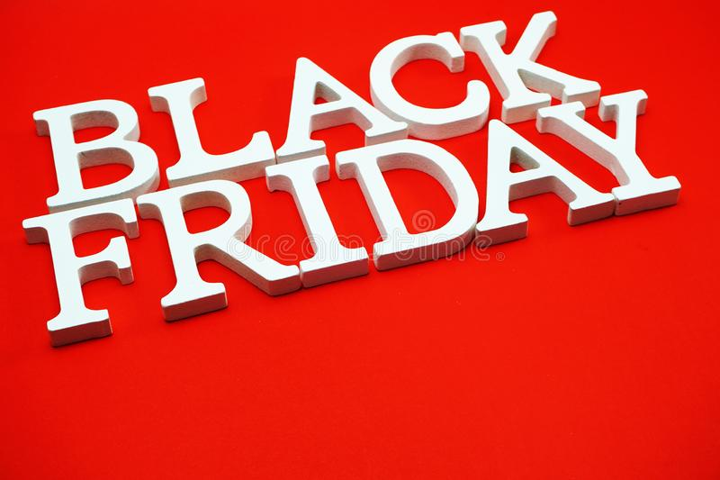 Alphabet de concept d'achats de vente de Black Friday sur le fond rouge image stock
