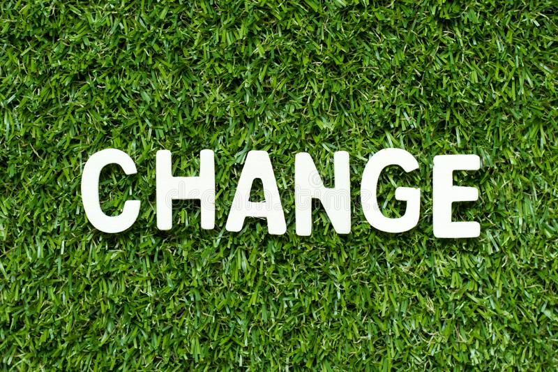 Alphabet in word change on artificial green grass background. Alphabet letter in word change on artificial green grass background stock image